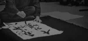 Masaaki Hatsumi painting in his dojo